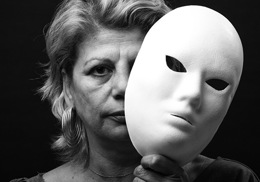 A woman removes a theatrical mask